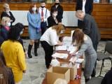 Maturzyści przy stole odbierają dokumenty