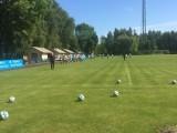 Piłki leżące na murawie boiska z zawodniczkami w tle