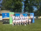 Drużyna piłkarska na murawie pozuje do zdjęcia grupowego